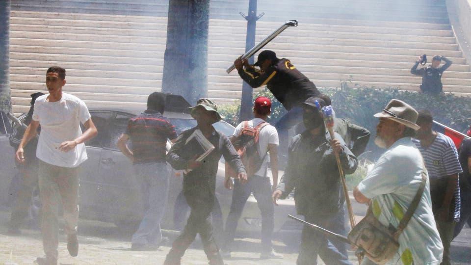 Un grupo de presuntos simpatizantes del Gobierno venezolano rompiendo un auto en las afueras de la Asamblea Nacional. Foto: Reuters / Carlos Garcia Rawlins
