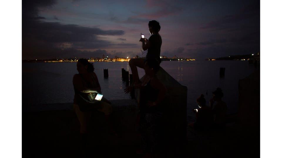 La gente se conecta a Internet en un punto de acceso en Regla, provincia de La Habana