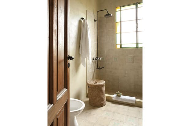 """La casa cuenta con dos baños en suite realizados en microcemento con revestimiento calcáreo color hueso. A los sanitarios, en lugar de mochila, se les hizo un depósito superior para """"tirar la cadena"""", como antes.."""