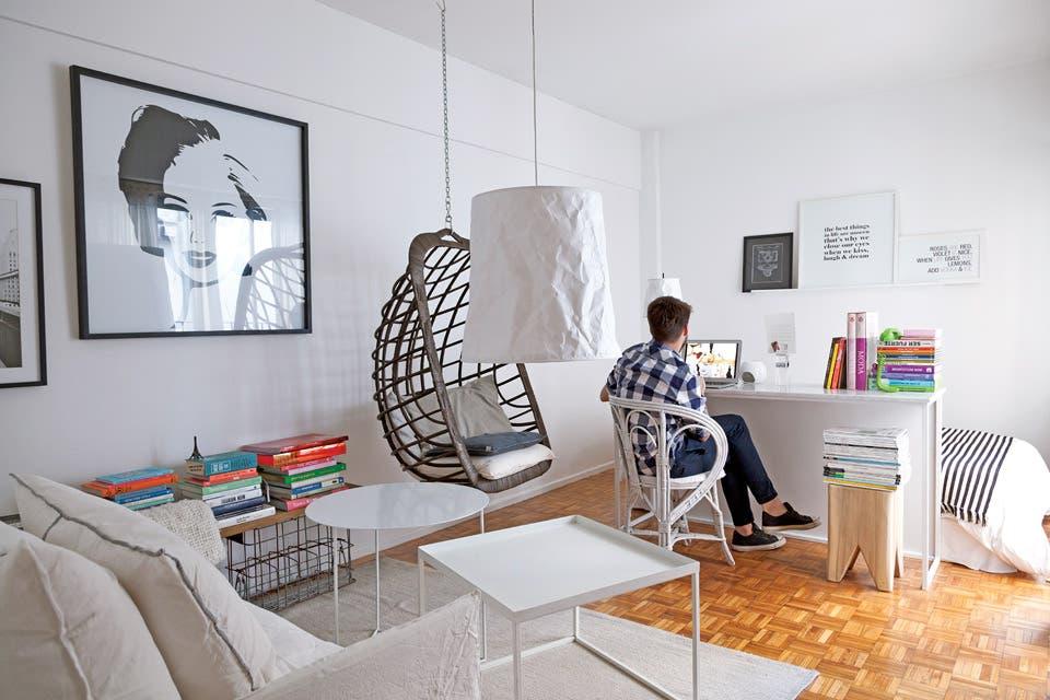 """Una alfombra (Las Zainas) delimita el estar con sillón con fundas de algodón (Hands Off!), hamaca de ratán (""""Lo último que puse; cuando la colgaron dije: ya está""""), mesas de hierro y lámpara de papel arrugado (Iluminación Agüero). Escondida detrás del escritorio, cama con funda de edredón blanca y p.  Foto:Living /Magalí Saberian"""