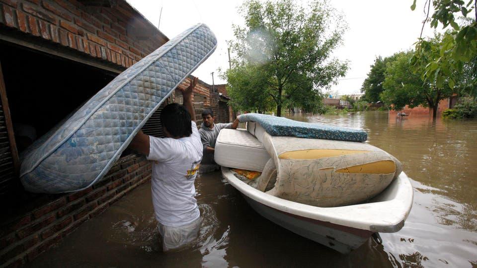 Los vecinos afectados tratan de salvar todo lo posible antes de que se lo lleve el agua. Foto: LA NACION / Mauro V. Rizzi /Enviado especial