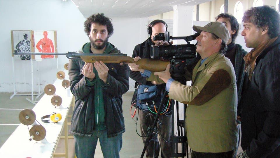Frenkel mira desde atrás la toma con Mario, que sostiene el rifle durante el rodaje de Amateur (2011)