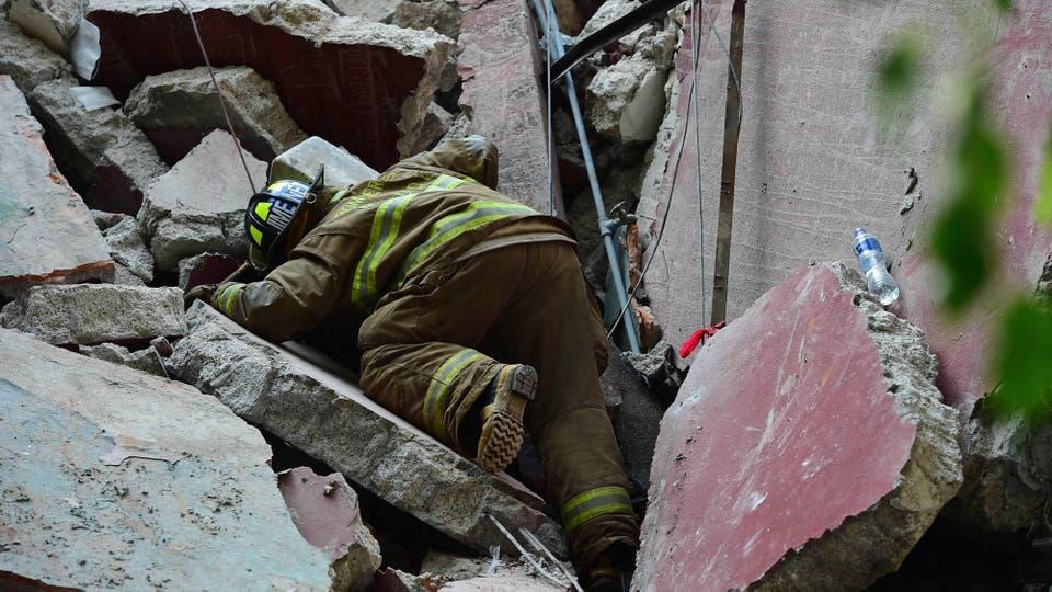 Un bomberos busca sobrevivientes entre los escombre de un edificio derrumbado. Foto: AFP