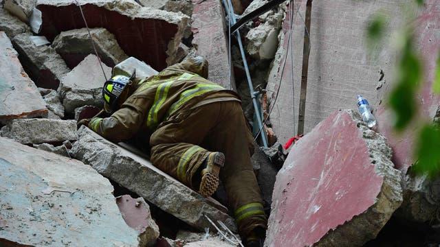 Un rescatista buscando entre los escombros