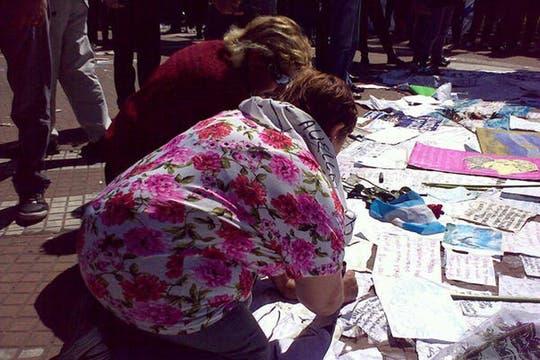 Dos mujeres suman su mensaje al homenaje armado en el piso de la Plaza. Foto: lanacion.com / @msolamaya