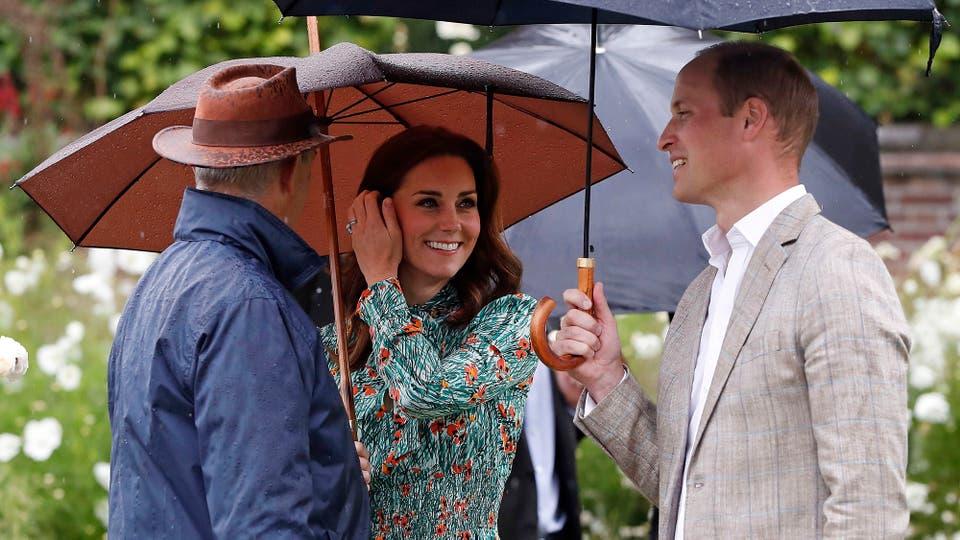 El Príncipe William, duque de Cambridge, y su esposa Catherine, duquesa de Cambridge, se refugian de la lluvia debajo de paraguas en los jardines de Kensington. Foto: AP / Kirsty Wigglesworth