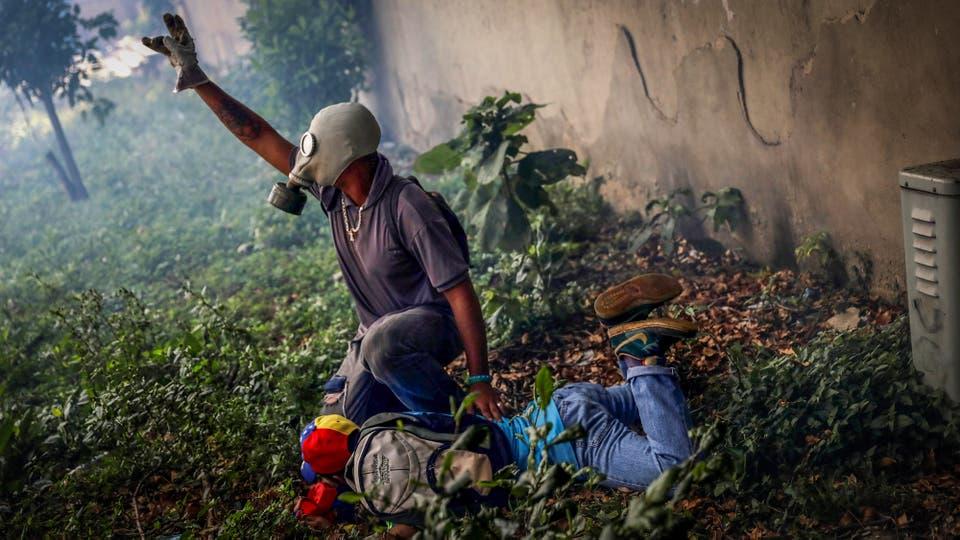Un manifestante ayuda a otro herido por los enfrentamientos con la policía. Foto: Reuters / Carlos Garcia Rawlins