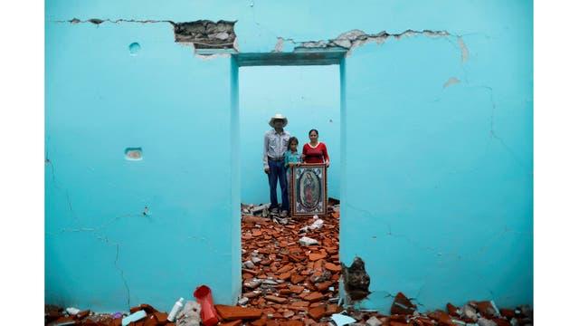 Luis Medina, de 36 años, trabajador rural, María Teresa Espinoza, de 35 años, ama de casa, y María de Jesús Medina, de 9 años, dentro de su casa que fue gravemente dañada después del terremoto en San José Platanar