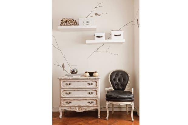 El dúo de sillones retapizados en cuero vienen de su cuarto de soltera. En las paredes, estantes flotantes laqueados (María Gándara Muebles) y un motivo de pájaros pintados (Blanco y Madera)..