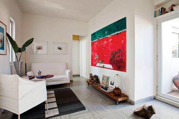 Sobre los mosaicos de los años 60, sofá de la misma década (Mercado de Pulgas) con funda de bull blanco. El sillón individual es un diseño de Philippe Starck. Alfombra de lana hecha en telar (Elementos Argentinos)..