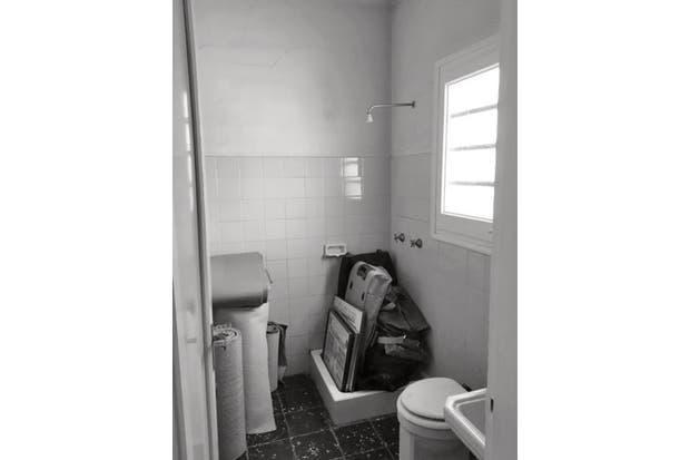 El baño, cuadrado y reducido, estaba revestido con azulejos verdes y piso cerámico negro. La pequeña ducha estaba en un rincón. .