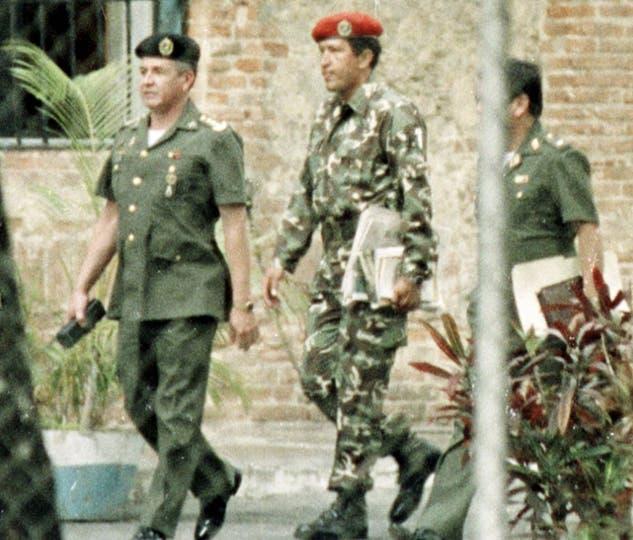Hugo Chávez, al centro, es escoltado por oficiales de inteligencia militar, tras ser detenido por tratar de derrocar al gobierno de Venezuela en un golpe de Estado. Foto: AP