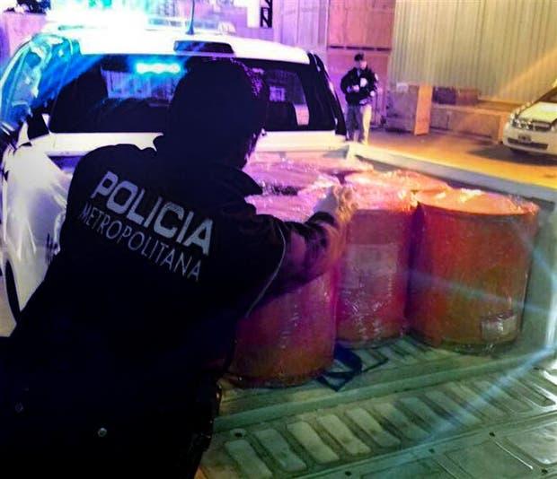 Los tambores con la droga son cargados en una camioneta de la Policía Metropolitana