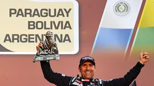 Stephane Peterhansel festeja su triunfo; detrás, el cartel de los tres países que organizaron la carrera en 2017; el año próximo la carrera podría volver a Chile