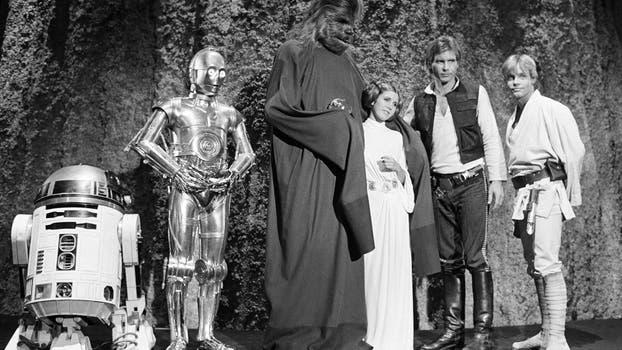 """Foto de archivo de 1978, muestra desde la izquierda, Kenny Baker, Anthony Daniels, Peter Mayhew, Carrie Fisher, Harrison Ford, y Mark Hamill durante el rodaje del especial de televisión de la CBS """"The Star Wars Holiday"""" en Los Ángeles. Foto: AP / George Brich"""