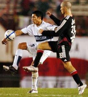 Escobar se lleva la pelota ante la marca de Gonzalo Higuain, que se destacó en su debut en River