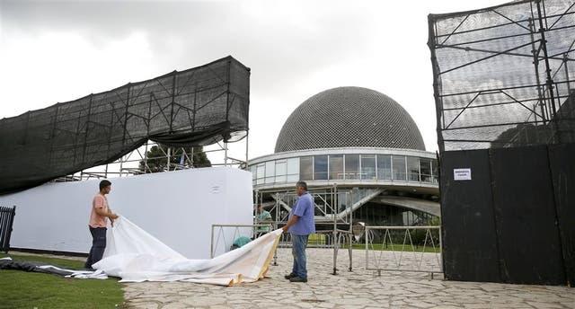 Dos operarios cierran el cerco perimetral que rodea el Planetario para el inicio de la renovación