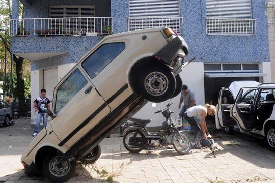 Un auto parece hacer equilibrio tras haber sido arrastrado por el agua. Foto: EFE