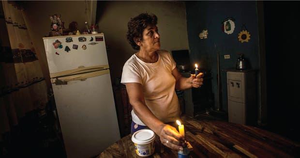Los apagones afectan a todos, como Nadia Rodríguez, que tiene que alumbrarse con velas durante las horas de racionamiento