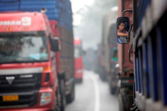 Un camionero reflejado en el espejo retrovisor de su vehículo durante un atasco en una autopista de Beijing, China. Foto: EFE