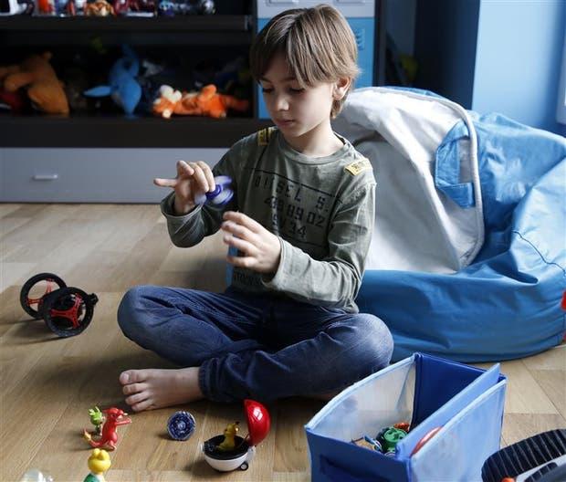 Massimo, de ocho años, junto a sus muñecos de Pokémon y su spinner