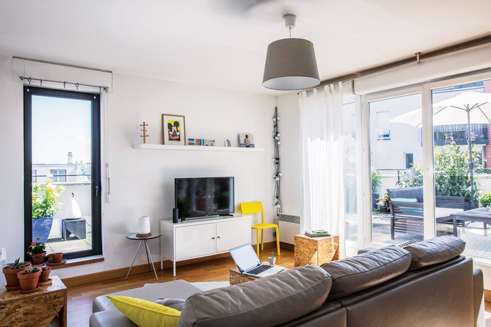 Mueble blanco y silla amarilla de Ikea. La mesa de tres patas con tapa de vidrio (Habitat) sostiene un jarrón de Hema, una gran tienda holandesa