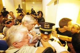 Turistas forcejeaban ayer con guardias de seguridad en un intento de ingresar en las oficinas de la compañía aérea en busca de información