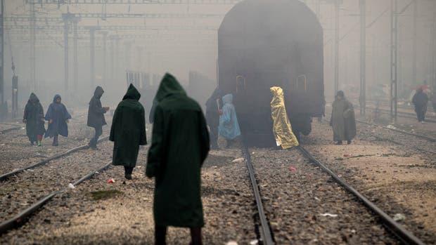 Refugiados caminan entre las vías del tren en Idomeni, Grecia