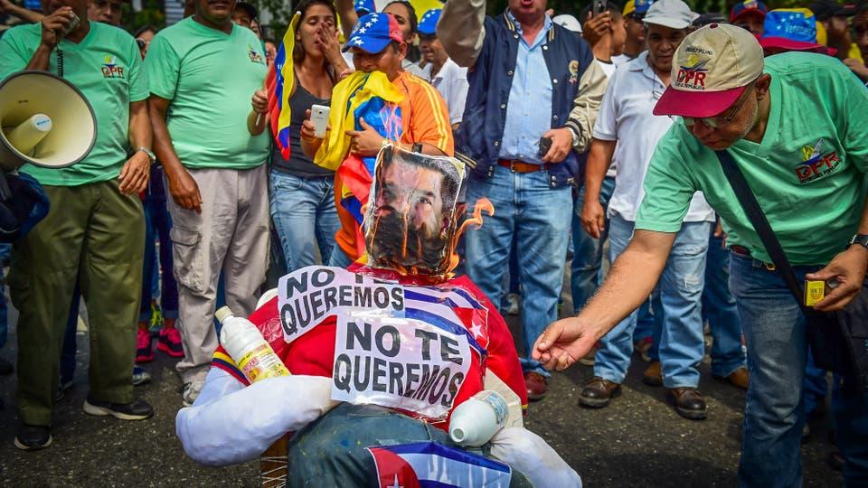 Manifestantes queman un muñeco con la cara de Nicolás Maduro . Foto: AFP / Ronaldo Schemidt