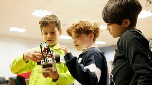 Máximo, Tiago y Marcio debaten sobre el diseño de un robot en el curso Robotito del ITBA