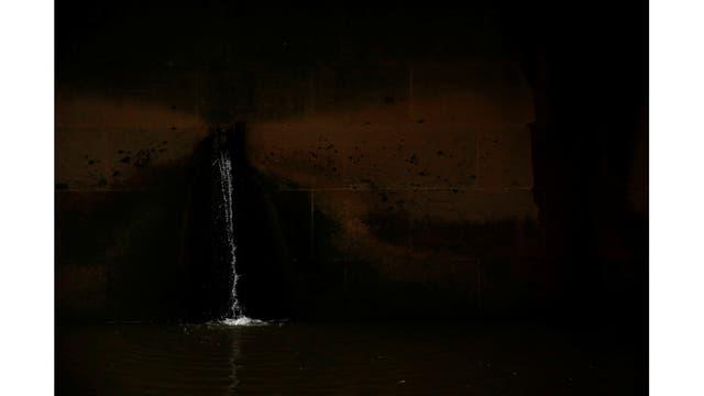 El agua sale de un puente sobre la orilla