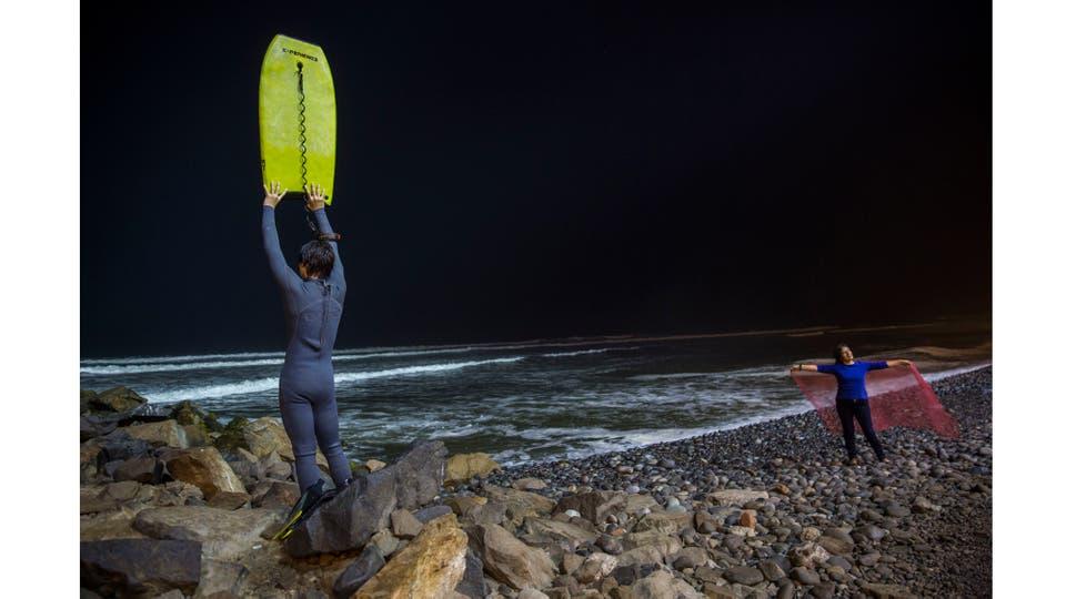 Renato de Negri de 15 años levanta su tabla para avisarle a su compañero que ha regresado a la playa. Foto: AP / Rodrigo Abd