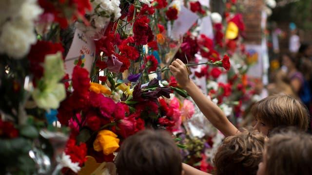 Un jóven catalán pone una flor en el colegio Ramón Llull donde el domingo se vivió uno de os episodios de represión más graves durante las votaciones. Foto: AP / Emilio Morenatti