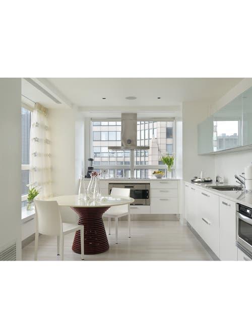 Cotidiano: una cocina superluminosa encuentra el máximo confort con pocos elementos. Las flores, frescas en los jarrones de vidrio, y las cortinas tramadas aportan calidez.