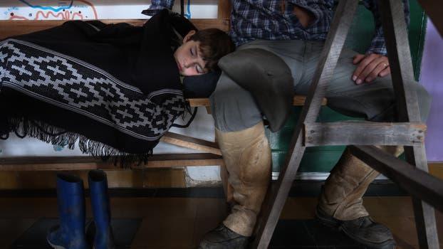 Francisco de 7 años descansa junto a su padre antes de continuar la travesía. Foto: LA NACION / Diego Lima