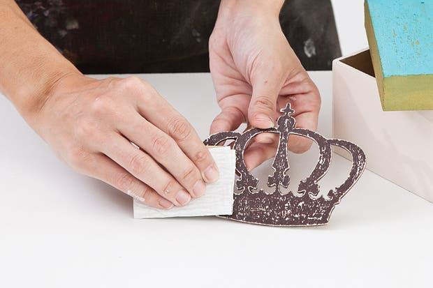 3. Sobre la corona, frotar nuevamente la vela y luego pintar con acrílico siena tostado, dejar secar y repetir el procedimiento anterior de lijado..