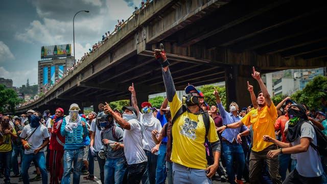 Manifestantes de la oposición se enfrentan a la policía antidisturbios en Caracas. Foto: AFP / Ronaldo Schemidt