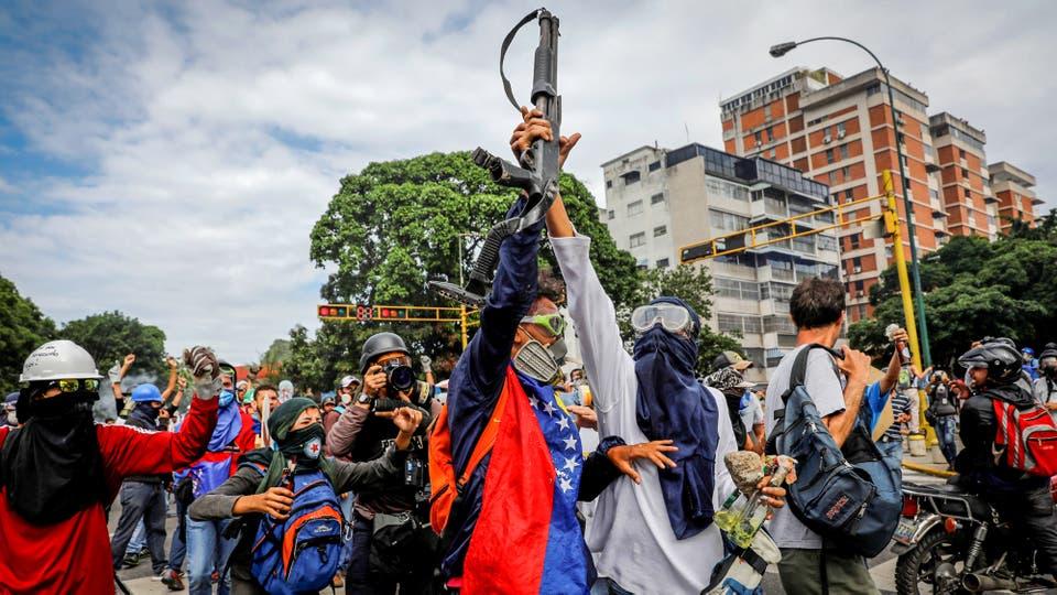 Manifestantes alzan una escopeta que robaron a un policía durante una manifestación en Caracas. Foto: Reuters / Carlos Garcia Rawlins