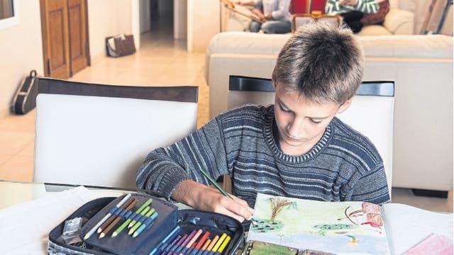 Marcos Garcilazo, de 12 años, pinta un libro que hizo él en la escuela Waldorf; una de sus hermanas, atrás, usa el celular