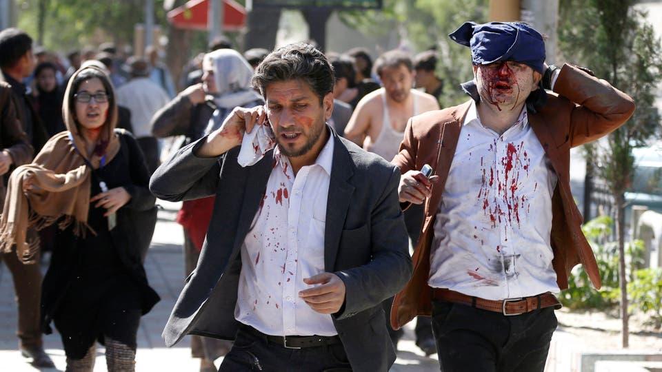 Dos jóvenes heridos caminan aturdidos en busca de atención médica . Foto: Reuters