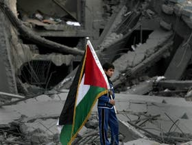 Un chico palestino rescata una bandera de entre los escombros en Gaza