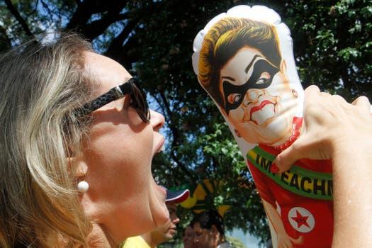 Una mujer sostiene un muñeco con la imagen de la presidenta Dilma Rousseff. Foto: EFE