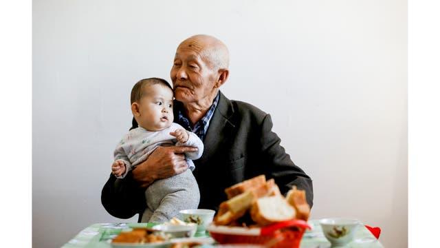 El ex pescador Sagnai Zhurimbetov, de 84 años, sostiene a su bisnieto de 10 meses Ykhlas en su casa en la antigua ciudad marítima de Aral