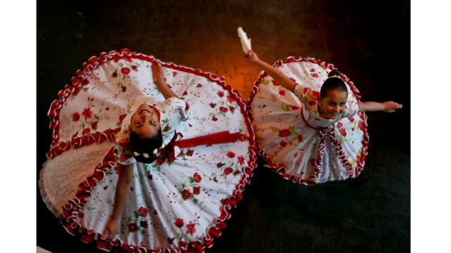 Josefa, de 13 años, y Selenna, de 8 años, posan para una foto vistiendo sus trajes tradicionales de baile chileno antes del evento que marca el Día del Niño Transgénero en Santiago de Chile