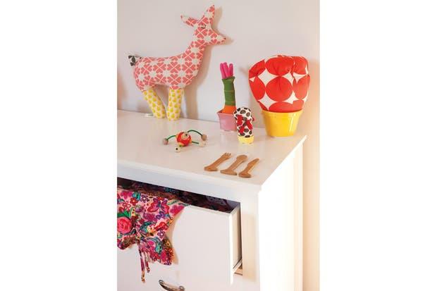 Sobre la cómoda (Vos te Reís), muñeco de tela ($75); cactus (de $42 a $130, ambos de Kom) y lámpara fucsia (Picnic)..