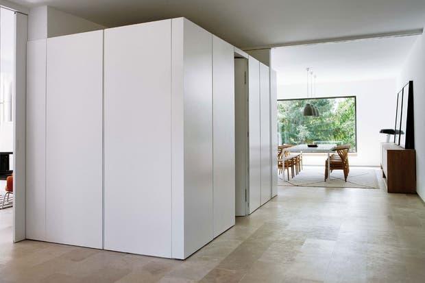 Un cubo blanco divide formalmente la zona de entrada del living. Contiene el toilette, rodeado por amplios armarios.  /Belén Imaz, gentileza Estudio Ábaton