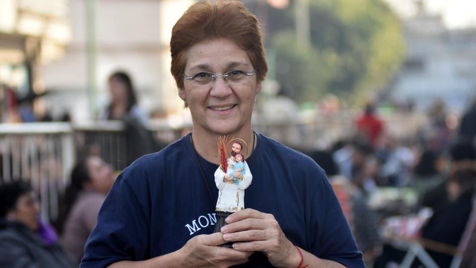 Una mujer muestra orgullosa su imagen de San Cayetano. Foto: DyN