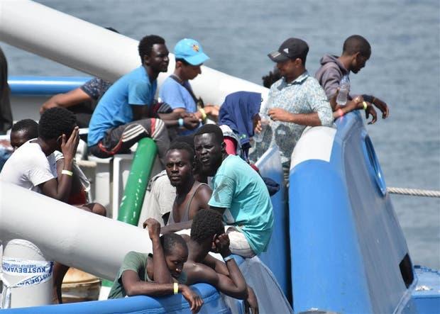 Inmigrantes rescatados del mar esperan para desembarcar en Italia