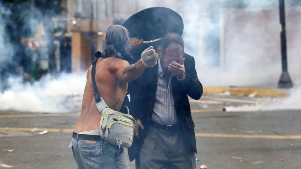 Un manifestante asiste a un hombre afectado por los gases . Foto: Reuters / Marco Bello