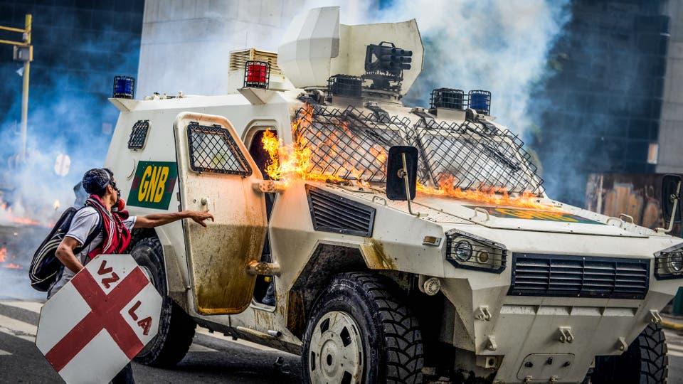 La policía antidisturbios abre la puerta de uno de sus vehículos luego de ser golpeados por una bomba molotov. Foto: AFP / Federico Parra